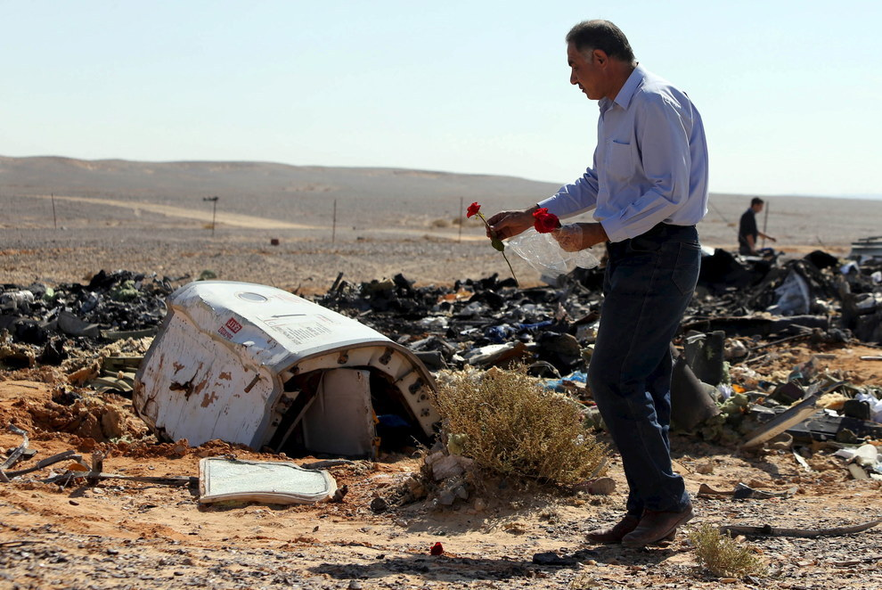 An Egyptian man lays flowers at the scene of the Russian passenger plane crash in Egypt's North Sinai.