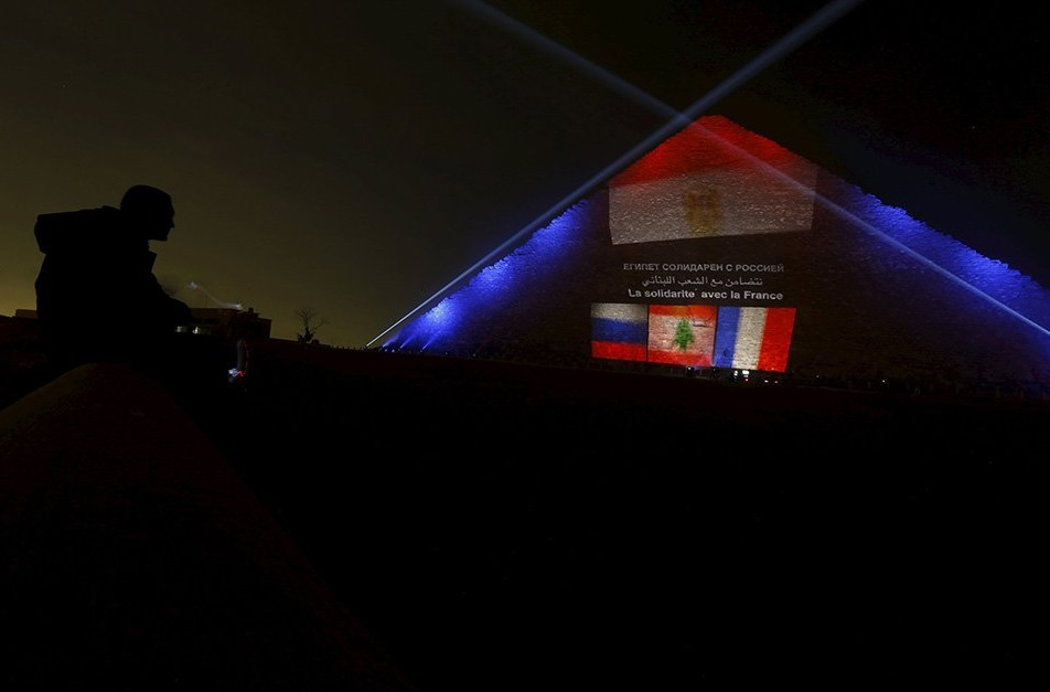A man looks on as the Russian, Lebanese and French flags are projected on one of the Giza pyramids, in tribute to victims from the respective countries, on the outskirts of Cairo, Egypt, November 15, 2015. REUTERS/Amr Abdallah Dalsh