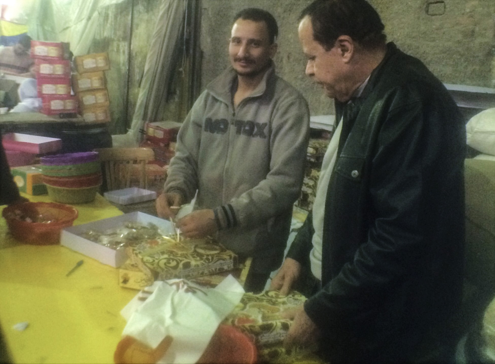 Packing el-Moulid sweets in Bein el-Harat Street. Phone photo by Nayrouz Talaat.