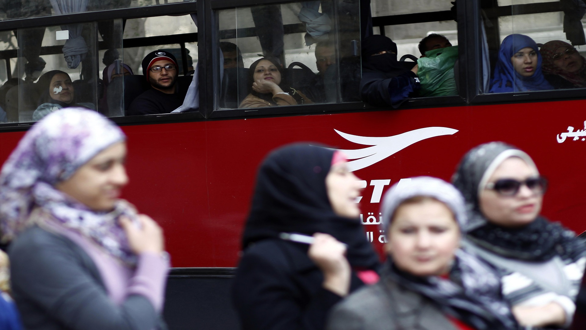 Egyptians ride in a bus past a polling station in central Cairo on December 15, 2012. (MAHMUD KHALED/AFP/Getty Images)