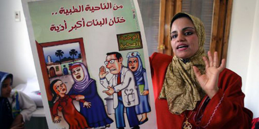 Mona Omar, a social worker, holds an FGM-awareness poster at a village meeting. Photo: Giacomo Pirozzi/UNICEF