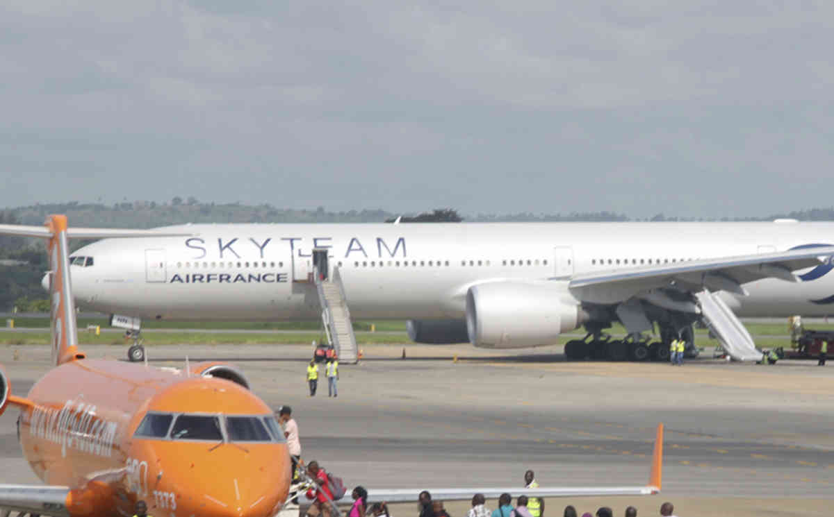An Air France plane which made an emergency landing is seen behind passengers boarding on a small jetliner at Moi International Airport in Mombasa, Kenya Sunday, Dec. 20, 2015. The Boeing 777 Air France flight 463 from Mauritius to Paris was forced to land in the Kenyan coastal city of Mombasa after a device suspected to be a bomb was found in the lavatory, a Kenyan police official said Sunday. The passengers shown in this photo are not the Air France plane evacuees. (AP Photo/Edwin Kana)