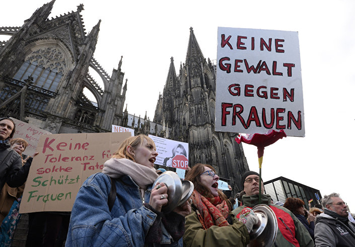 "A man holds up a sign reading ""No violence against women"" as he takes part in a demonstration in front of the cathedral in Cologne, western Germany, on January 9, 2015 where sexual assaults in a crowd of migrants took place on New Year's Eve. Photo: AFP"