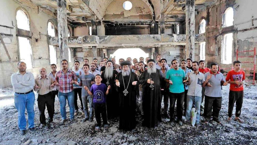 Coptic Christians pray in a burned church in Egypt in 2013.