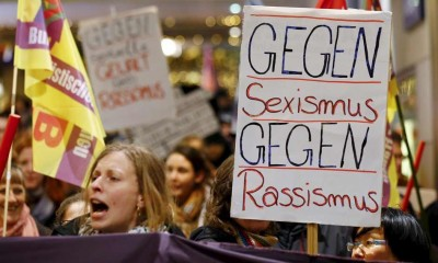 """Women shout slogans and hold up a placard that reads """"Against Sexism - Against Racism"""" as they march through the main railways station of Cologne, Germany, on January 5 (Reuters)"""