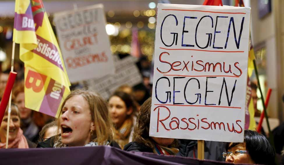 "Women shout slogans and hold up a placard that reads ""Against Sexism - Against Racism"" as they march through the main railways station of Cologne, Germany, on January 5 (Reuters)"
