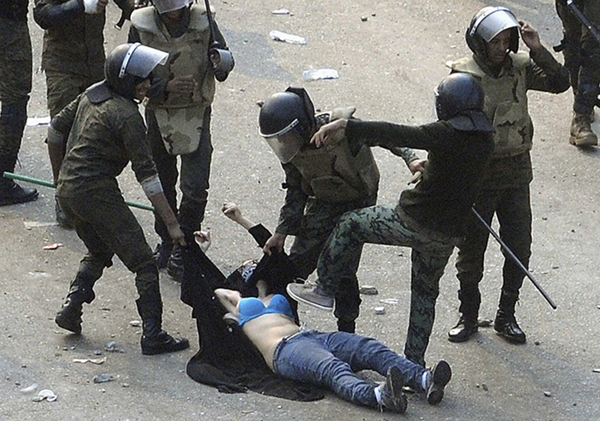 Egyptian soldiers beat a female protester during clashes at Tahrir Square, pulling up her abaya and dragging her through the street. Photo: Reuters