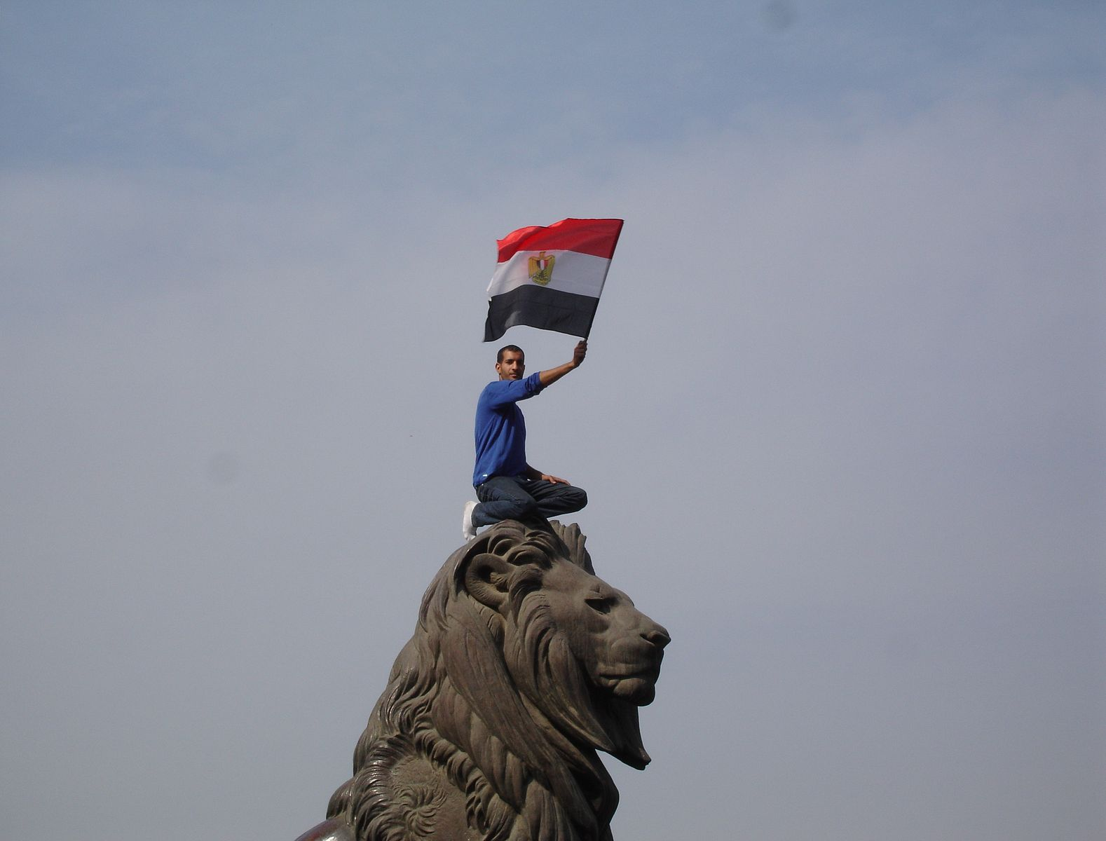 An Egyptian man sits atop one of the lions at the entrance of Kasr El Nil Bridge, leading to Tahrir Square on February 1, 2011. Photo: Zeinab Mohamed