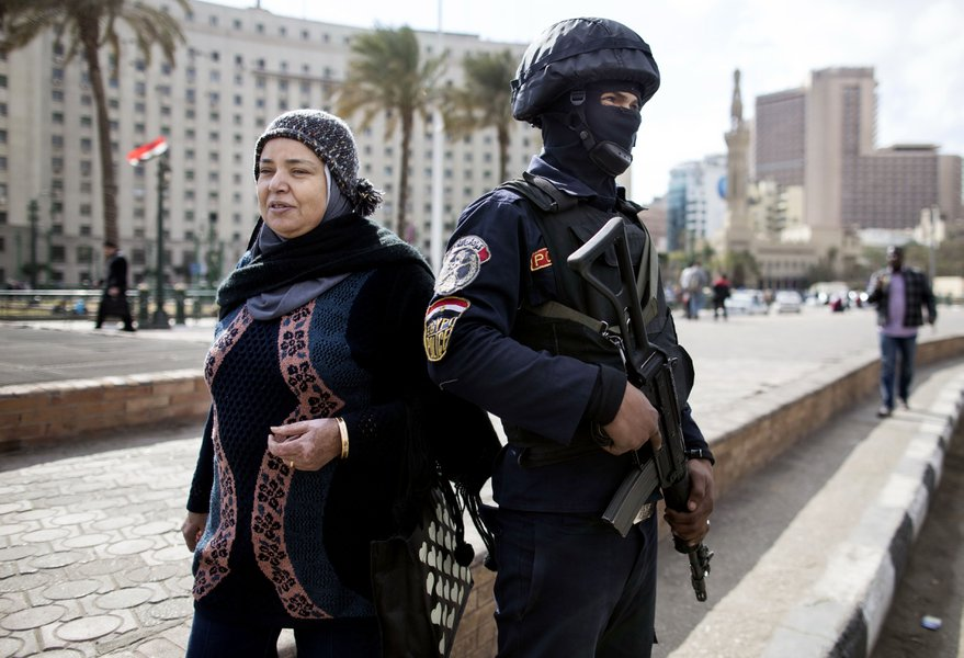 A woman walks past a security officer at Tahrir Square a day ahead of the January 25 Revolution's anniversary. Credit: AP