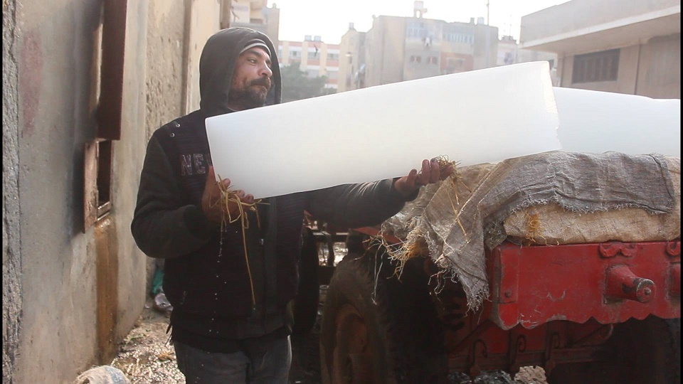 An ice factory worker carries ice blocks onto a truck. Photo: Aswat Masriya