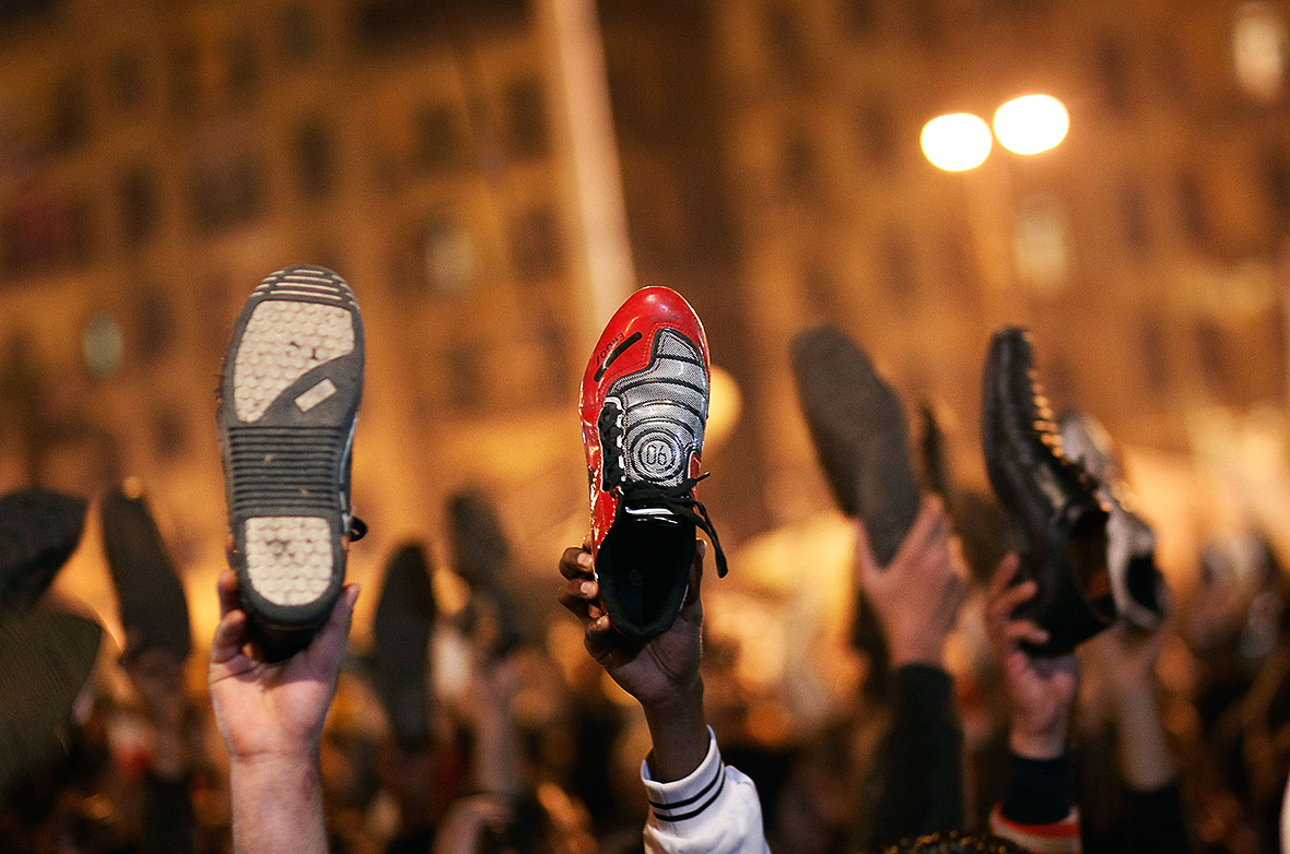 Anti-government protesters raise their shoes after a speech by Egyptian President Hosni Mubarek saying that he had given some powers to his vice president but would not resign or leave the country. Photo: Chris Hondros, Getty Images
