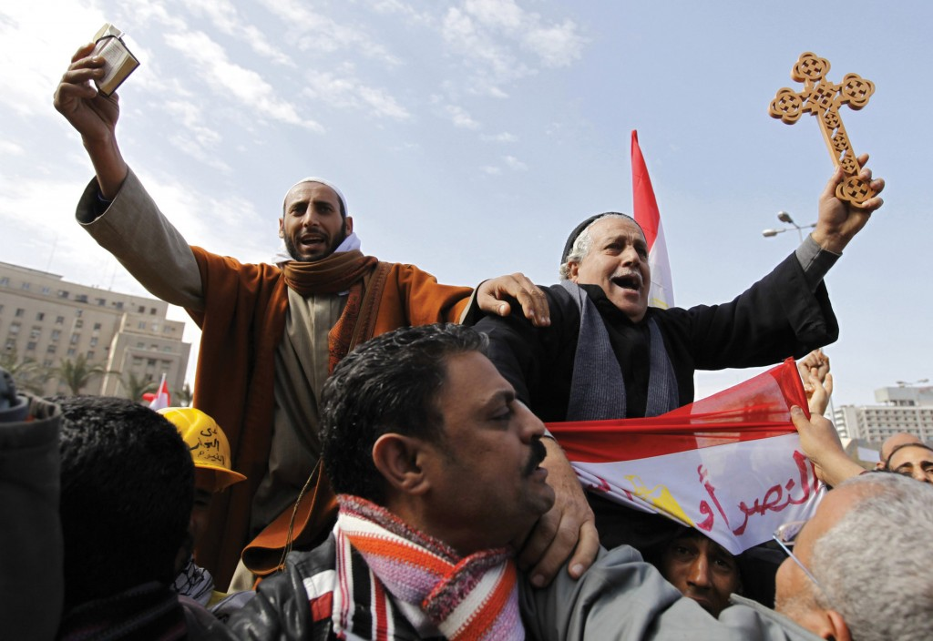 A Muslim holding the Quran (left) and a Coptic Christian holding a cross are carried through opposition supporters in Tahrir Square in Cairo February 6, 2011. Photo: Dylan Martinez, Reuters