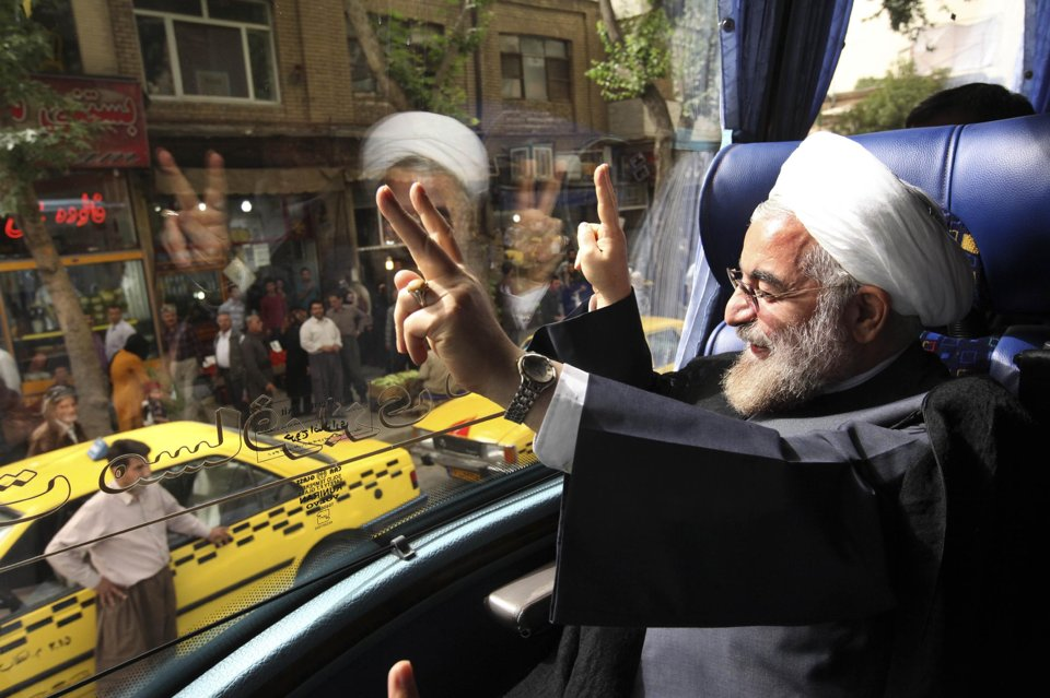 Iranian President Hasan Rouhani waves from his bus during his presidential election campaign tour in June 10, 2013, photo,. Credit: Vahid Salemi/ AP