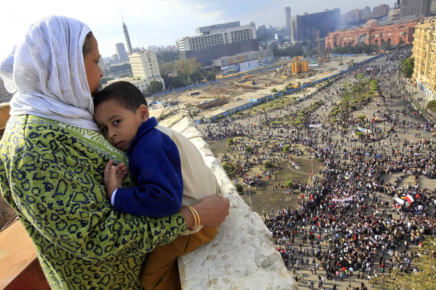 An Egyptian mother watched as thousands of Egyptian protesters gathered at Tahrir Square in Cairo in January 2011. The ruling National Democratic Party building can be seen burned at top right behind the Egypt museum. Photo: Amr Nabil, AP