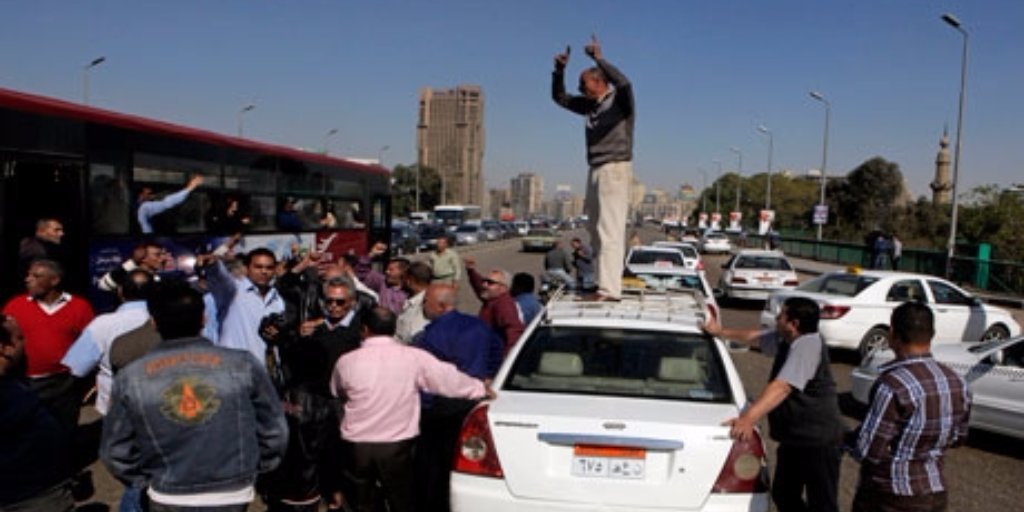 An Egyptian taxi driver stands on his car as he and others block part of the 6th October bridge in central Cairo, Egypt, 2013. Photo: AP