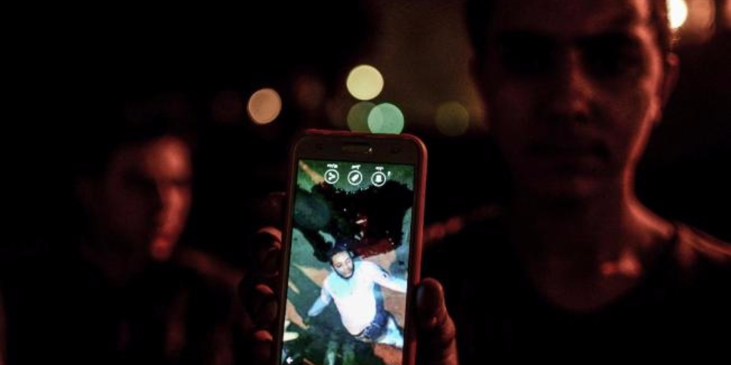 In this Thursday, Feb. 18, 2016 photo, a man shows a photo he took on his mobile phone of a driver who was killed by a police officer, in a dispute in Cairo, Egypt. (AP Photo)