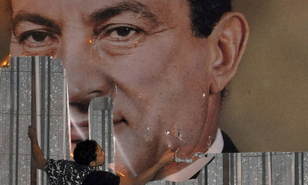 An anti-government protester defaces a picture of Egypt's President Hosni Mubarak in Alexandria on January 25, 2011. Photo: Stringer, Reuters