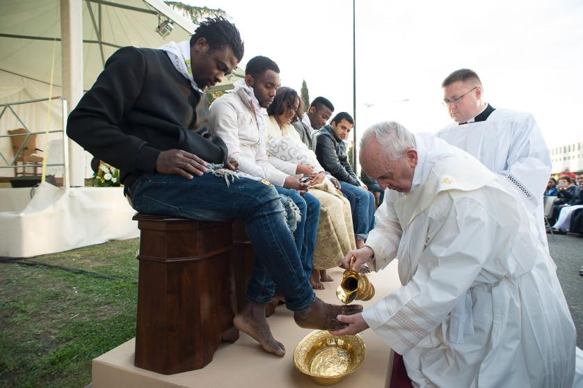 In this handout picture released by the Vatican Press Office, Pope Francis performs the foot-washing ritual at the Castelnuovo di Porto refugees center near Rome on March 24, 2016.