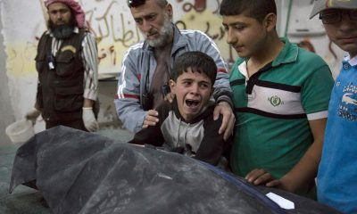 A Syrian boy is comforted as he cries next to the body of a relative who died in an airstrike on April 27 in the rebel-held neighborhood of al-Soukour in the northern city of Aleppo. (Karam Al-Masrik/AFP/Getty Images)