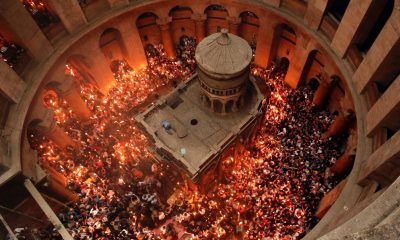 "Christian Orthodox worshippers hold up candles lit from the ""Holy Fire"" as thousands gather in the Church of the Holy Sepulchre in Jerusalem's Old City, on April 30, 2016. Credit: Thomas Coex, AFP"