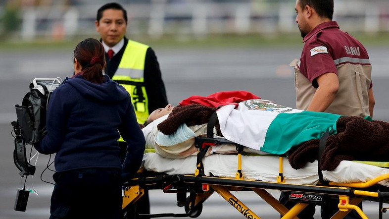 Paramedics wheel a Mexican tourist covered with a Mexican flag, who was injured during an attack in Egypt, toward a helicopter after their arrival to the presidential hangar in Mexico City, September 18, 2015. REUTERS/Tomas Bravo