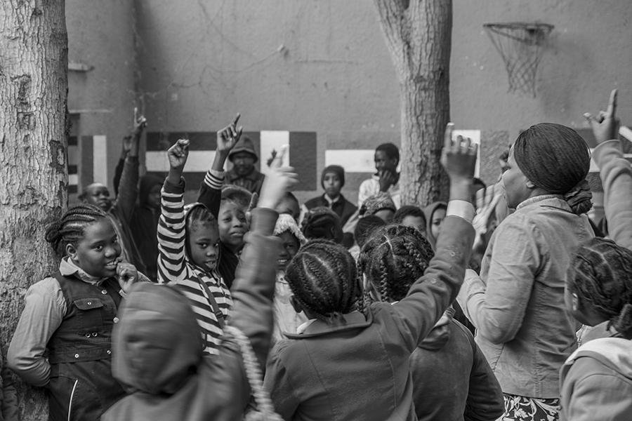 Kids raise their hands to answer their teacher