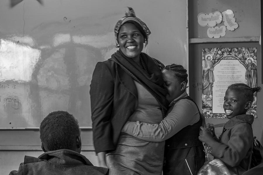 A girl cries and hugs her teacher