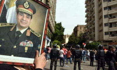 A supporter of President Sisi waves a of portrait of him as protesters gather outside the Journalists' Syndicate headquarters in Cairo on May 4, 2016. (Photo/AFP)