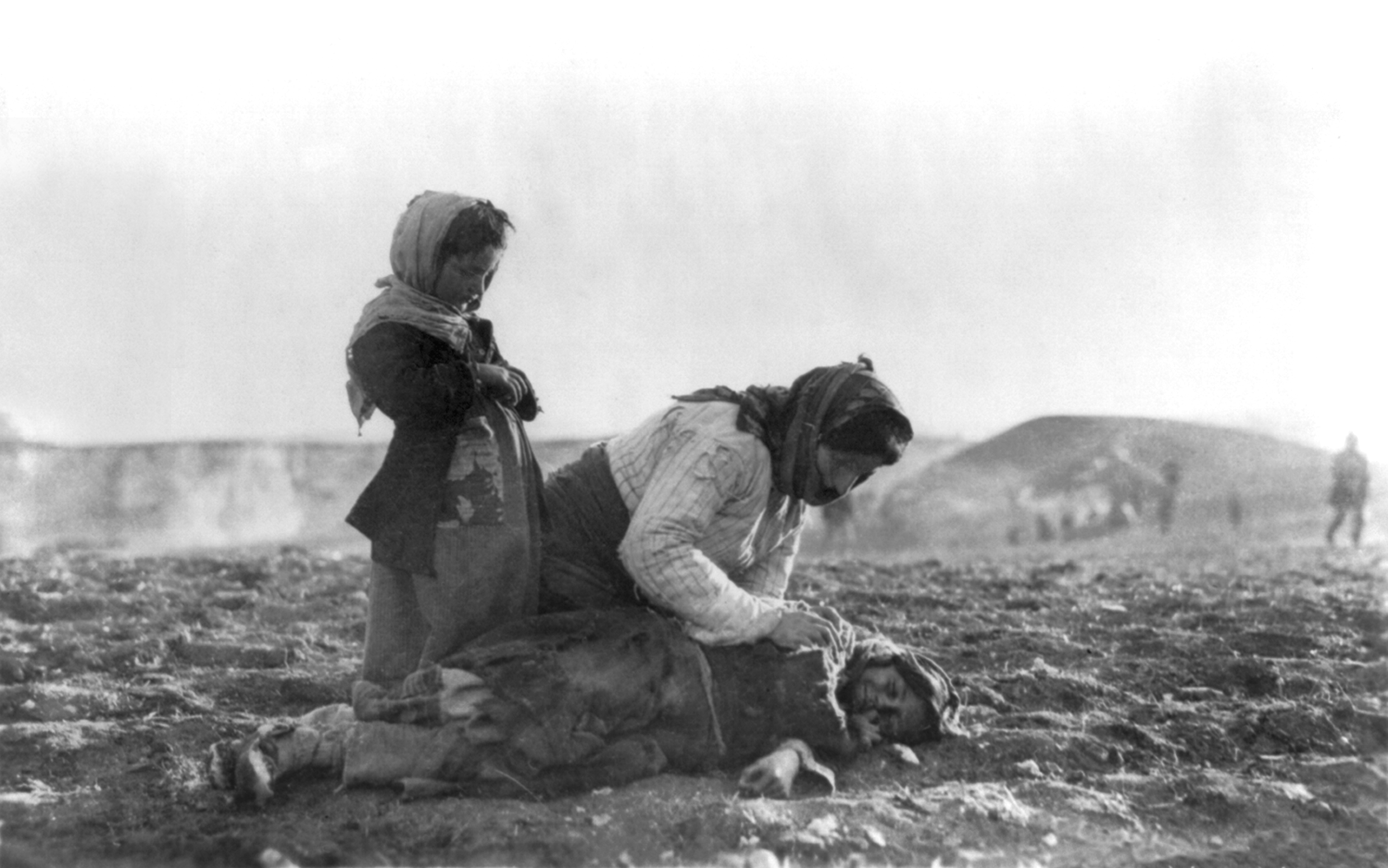 "An Armenian woman kneeling beside a dead child in field ""within sight of help and safety at Aleppo"" (Credit: Wikicommons)"