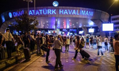 People stand outside the entrance as they leave the airport after two explosions followed by gunfire hit the Turkey's biggest airport of Ataturk in Istanbul, on June 28, 2016 (AFP Photo/Ozan Kose)