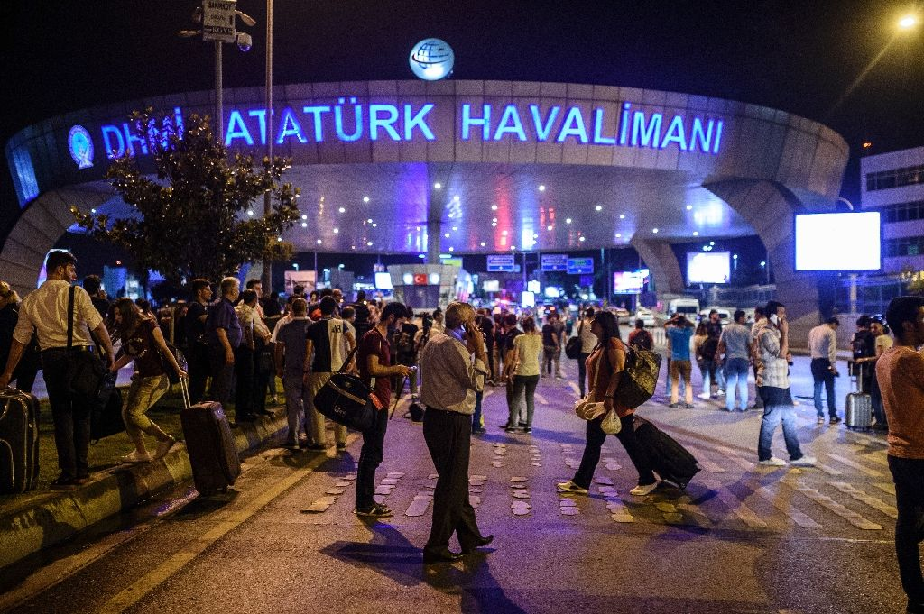 People stand outside the entrance as they leave the airport after two explosions followed by gunfire hit the Turkey`s biggest airport of Ataturk in Istanbul, on June 28, 2016 (AFP Photo/Ozan Kose)