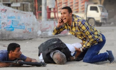 ournalist Tamer Magdy, without any vest or protection, cries for help and leaps to the side of Police General Nabil Farag
