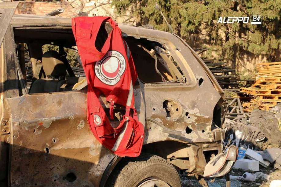 This image provided by the Syrian anti-government group Aleppo 24 news, shows a vest of the Syrian Arab Red Crescent hanging on a damaged vehicle, in Aleppo, Syria, Tuesday, Sept. 20, 2016. A U.N. humanitarian aid convoy in Syria was hit by airstrikes Monday as the Syrian military declared that a U.S.-Russian brokered cease-fire had failed, and U.N. officials reported many dead and seriously wounded. (Aleppo 24 news via AP)