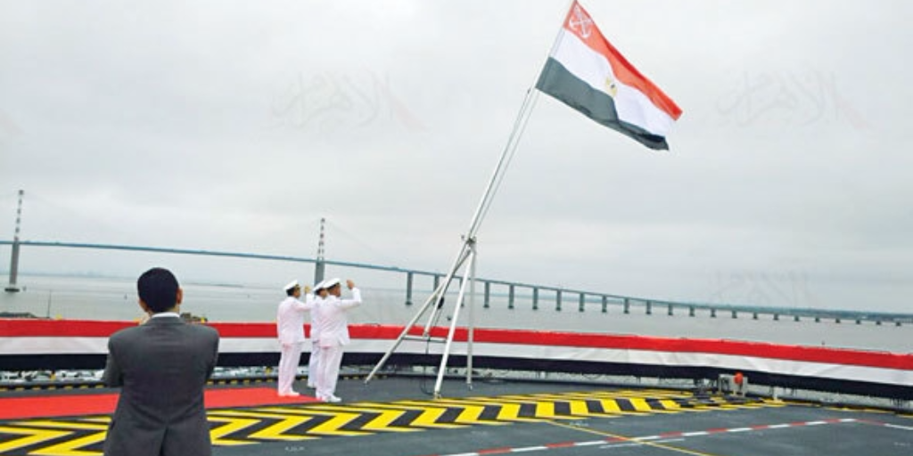 Snapshot from Egyptian TV shows Egyptian Navy officials raising the country's flag on its first-ever French Mistral helicopter carrier, named after late president Gamal Abdel Nasser, June 2, 2016