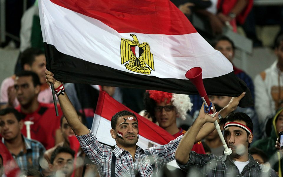 An Egyptian supporter waves a national flag during the World Cup qualifying playoff second leg soccer match, at the Air Defense Stadium in Cairo, Egypt, Tuesday, Nov. 19, 2013 (Photo: AP)