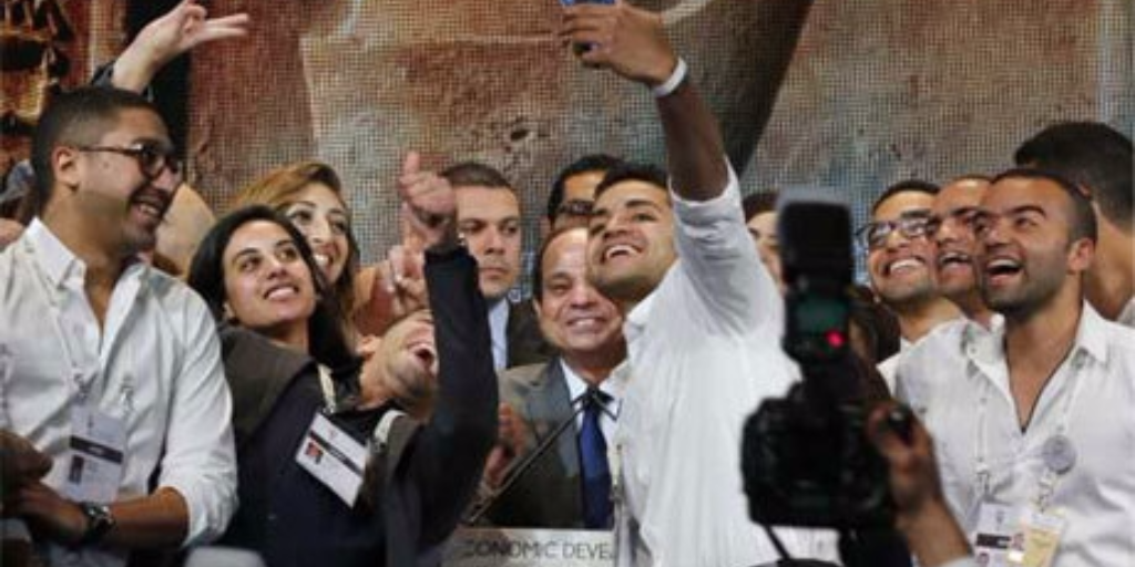 """Egypt's President Sisi smiles as young volunteers take a """"selfie"""" with him during the closing session of Egypt Economic Development Conference (EEDC) in Sharm el-Sheikh 15 March 2015 (Photo: Reuters)"""