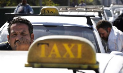 An Egyptian taxi driver peers over his car as he and others block part of 6th of October bridge in central Cairo, Egypt, Monday, March 25, 2013.  (AP Photo/Amr Nabil)