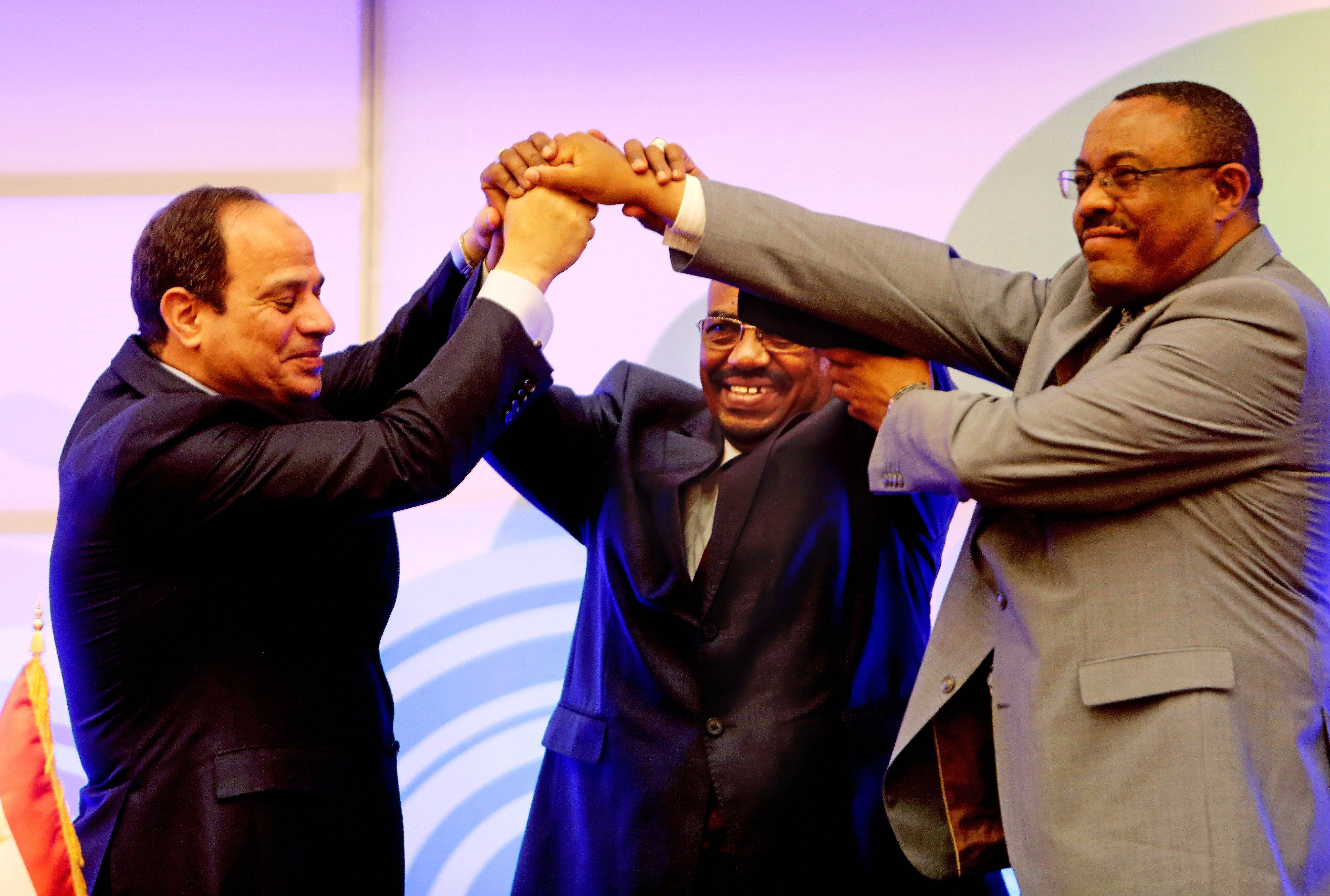 Sudanese President Omar al-Bashir, center, Egyptian President Abdel-Fattah el-Sissi, left, and Ethiopian Prime Minister Hailemariam Desalegn, right, hold hands after signing an agreement on sharing water from the Nile River, in Khartoum, Sudan, Monday, March 23, 2015. Egypt, Ethiopia and Sudan on Monday signed an initial agreement on sharing water from the Nile River that runs through the three countries, as Ethiopia constructs a massive new dam it hopes will help alleviate its electricity shortages. El-Sissi, al-Bashir and Desalegn welcomed the agreement in speeches in Khartoum's Republican Palace on Monday. (AP Photo/Abd Raouf)
