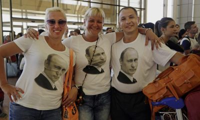 Russian tourists wearing t-shirts with images of Russian President Vladimir Putin pose for a photo in the departure terminal before  boarding a flight from Sharm el-Sheikh, south Sinai, Egypt, Friday, Nov. 6, 2015. Egyptian police carried out detailed security checks on Friday at the airport in Sharm el-Sheikh, the resort from where the doomed Russian plane took off last weekend, after U.K. officials confirmed that flights will start bringing stranded British tourists home from the Sinai Peninsula. (AP Photo/Thomas Hartwell)