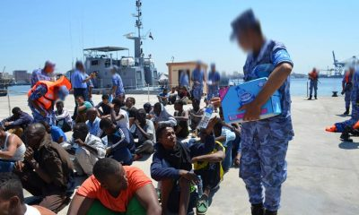 Navy officers appear to be handing out water bottles to a group of refugees who were prevented from illegally migrating in September 2015. Credit: Military Spokesman